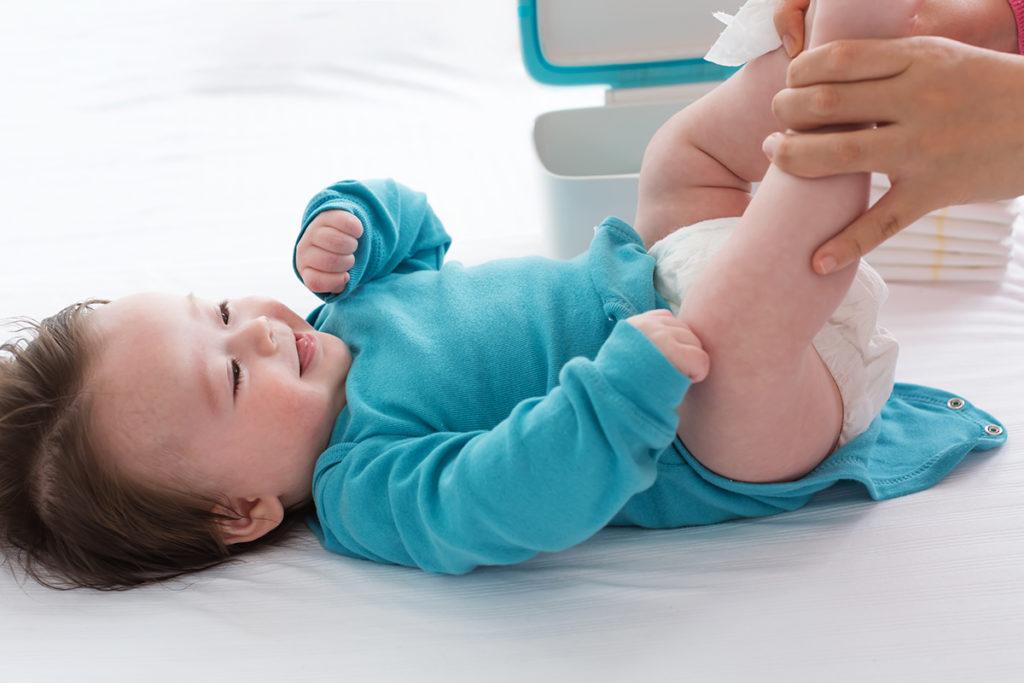 ベビーベッドでおむつ替えをする赤ちゃん